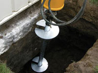 Installing a helical pier system in the earth around a foundation in Selkirk