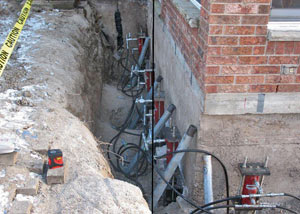 Foundation push piers installed around a house with a foundation settlement issues in Grande Pointe