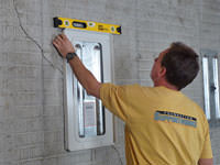 Positioning a wall plate cover on a foundation wall in Thompson.